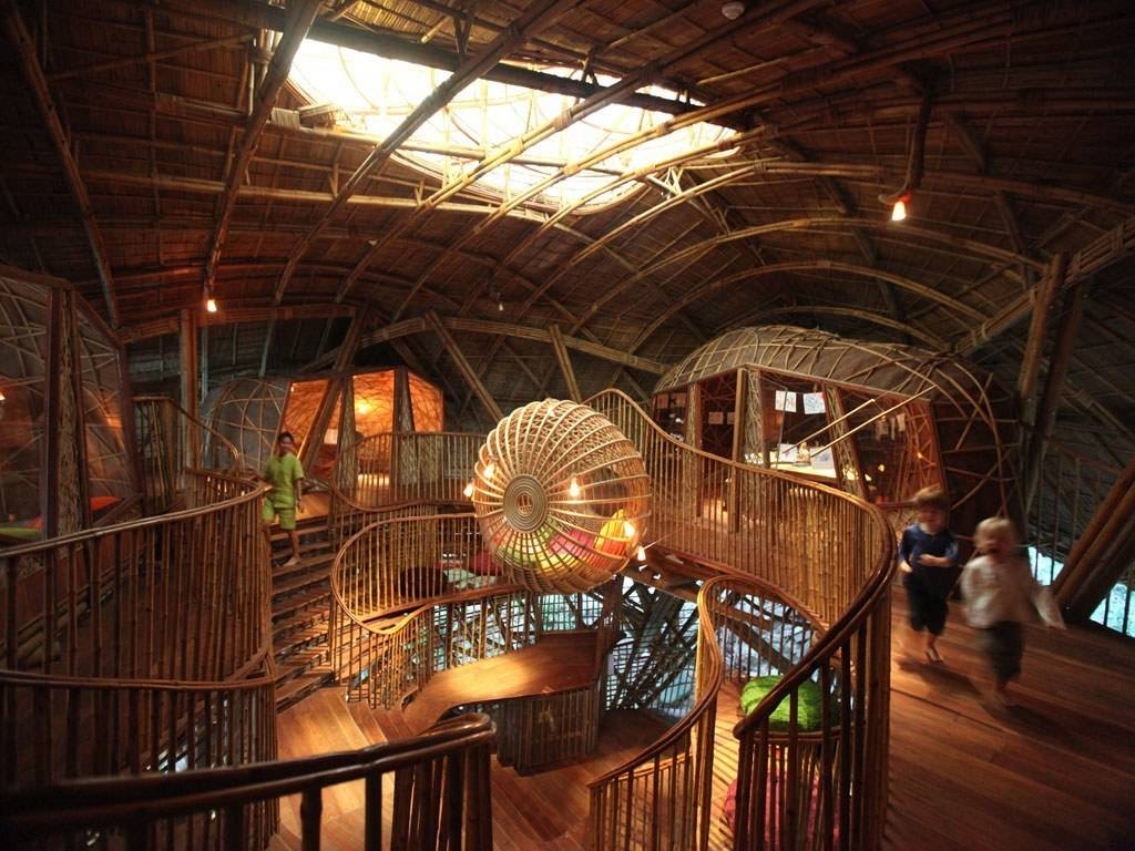 Inside image of kids club, made from wood and bamboo, kids running aorund