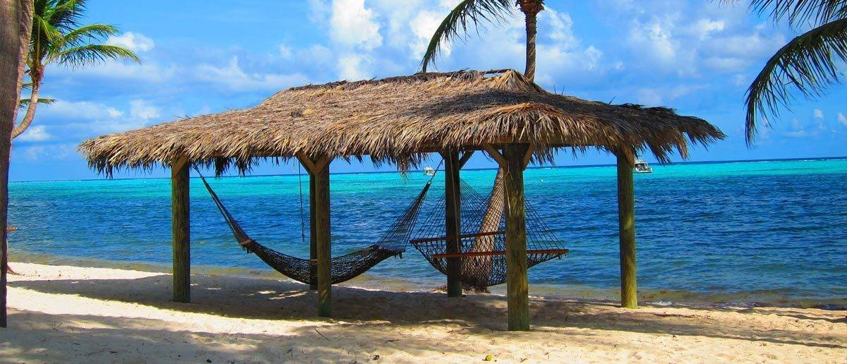 Traditional beach hut with two hammocks on beach in the Cayman Islands