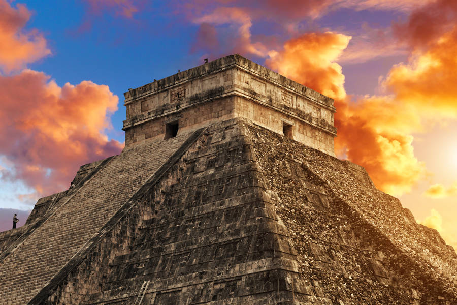 Sunset turns clouds red and orange over Chichen Itza, Mexico