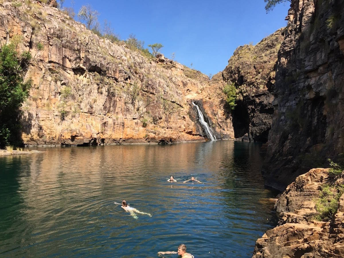 4 people swimming in a natural gorge in Kakadu National Park