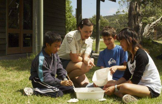 Park ranger teaching young kids about soil.