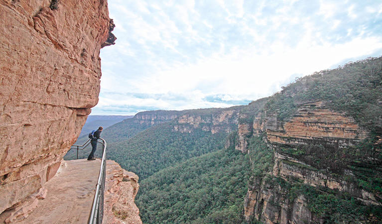 Hiker looks over ledge on the edge of mountain in the Blue Mountains