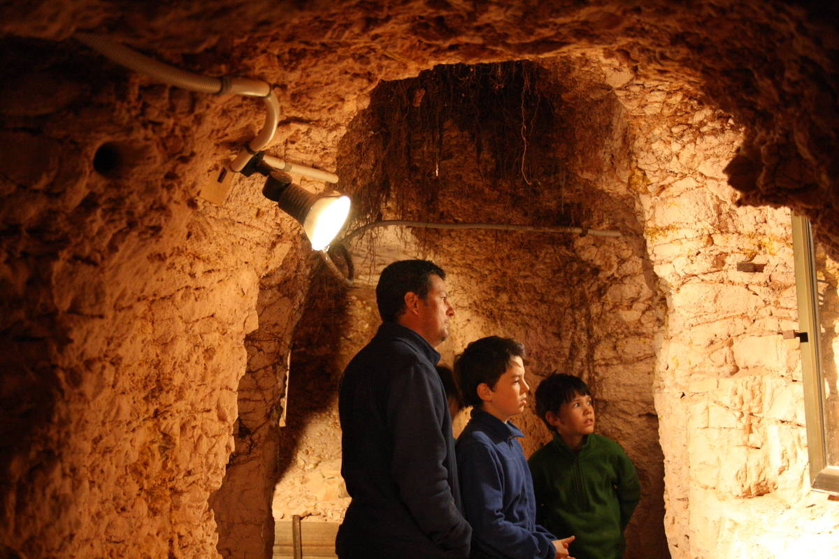 Two boys and their dad explore the caves underground at Coober Pedy