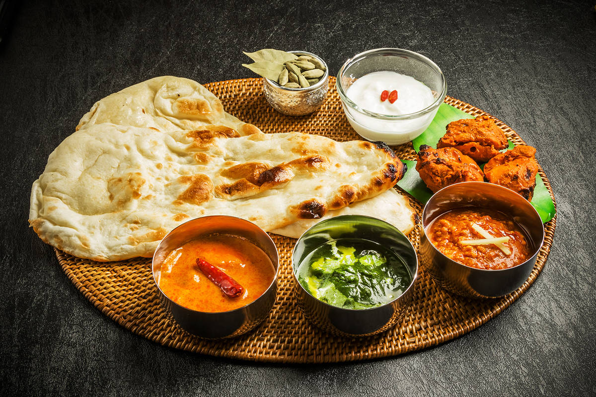 Indian dishes laid out on table with naan bread and toppings