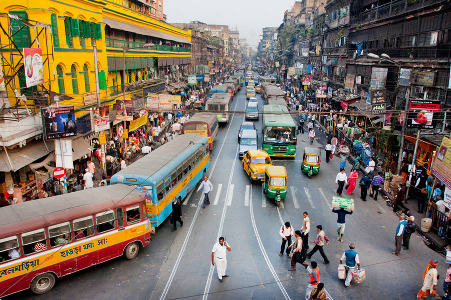 Bust street in Kolkata, India. Traffic and people on the road.