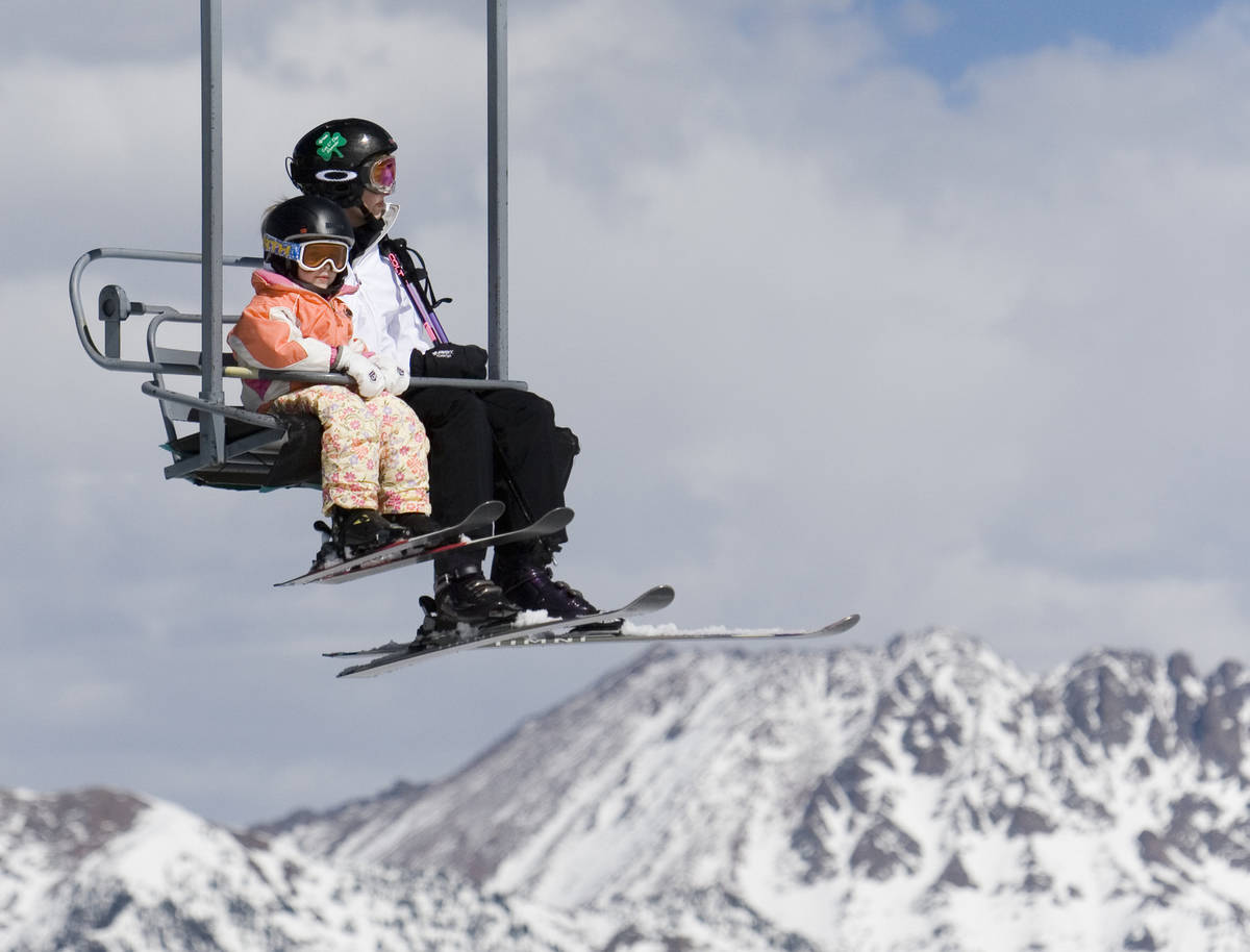 Mother and young daughter ride chairlift with mountains in background