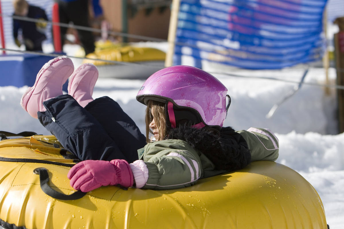 Young girl rides inflatable donut on ski slope