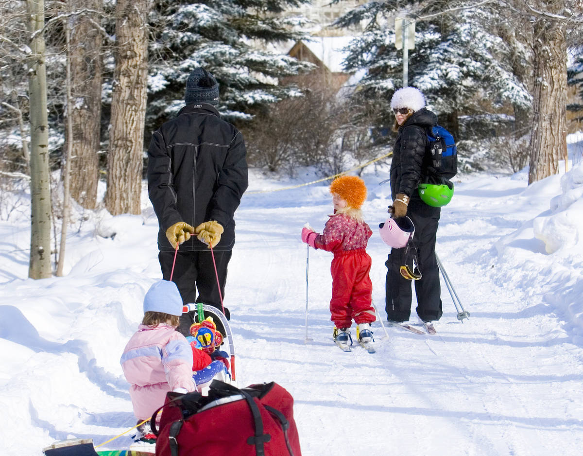 Two parents pulling their kids along on snowmobiles and skis