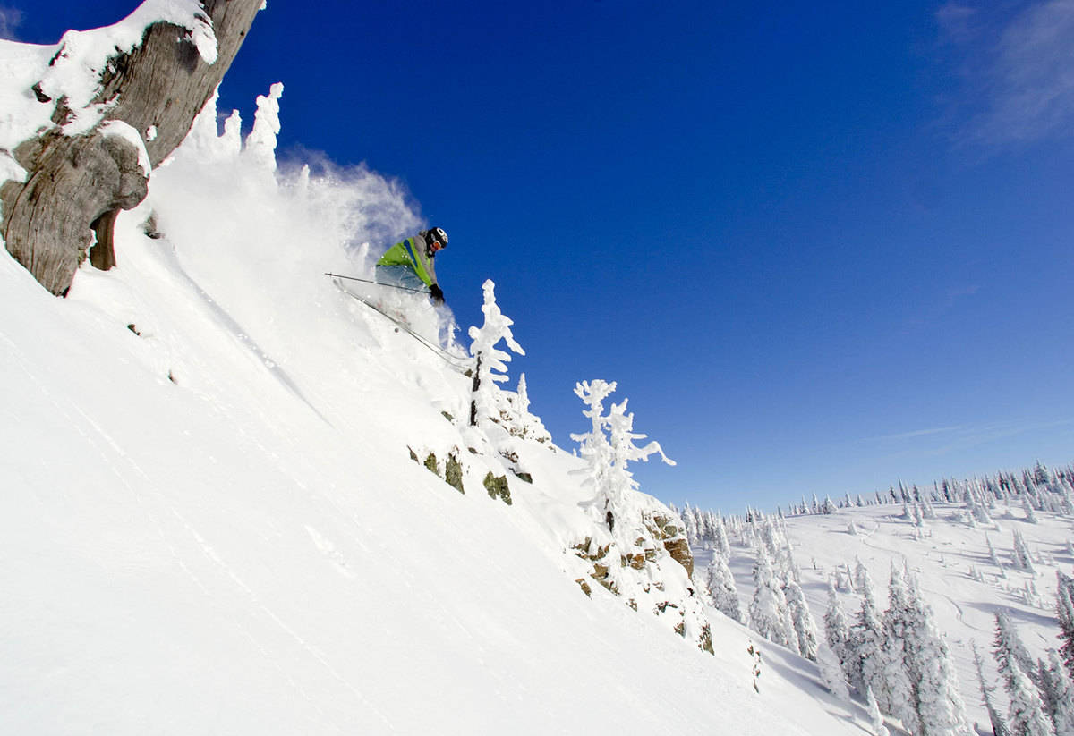 Skier flies down mountain with blue sky in background