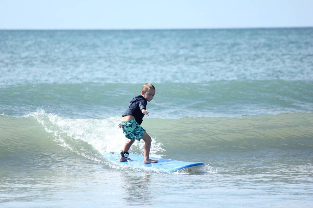 young boy learning to surf in summer