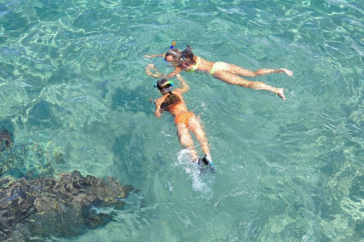 Two girls snorkelling in clear water during summer