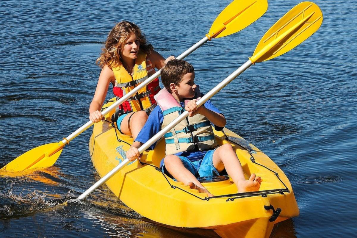 Two young kids paddling in kayak