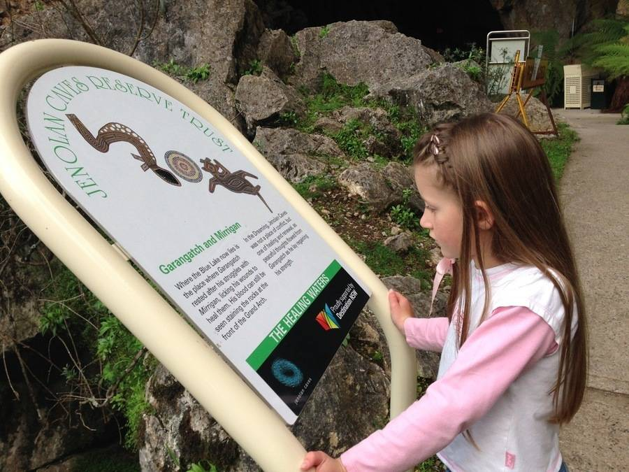 Young girl reads sign about Indigenous culture at Jenolan Caves, Blue mountains during school holidays