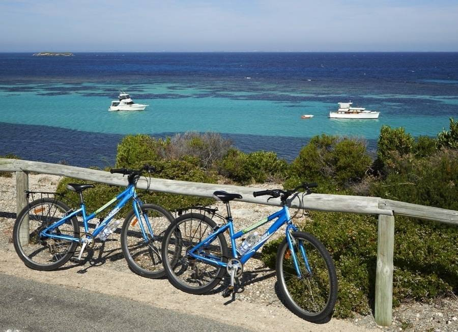 Bike leaning up against fence on Rottnest Island, blue water and boats in background