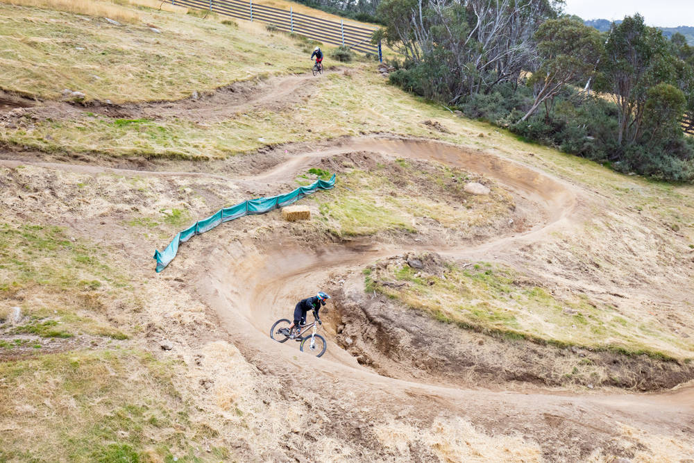 Mountain bikers descend down Thredbo on a cool autumn day in the Snowy Mountains, New South Wales, Australia.