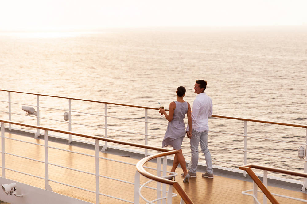 Couple on deck of cruise ship at sunset