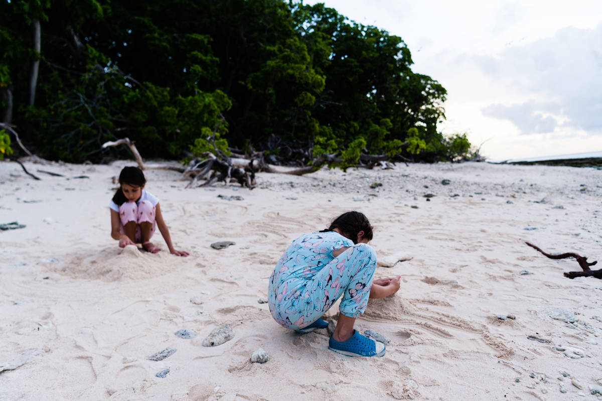 Two girls dig in the sand on Lady Musgrave Island