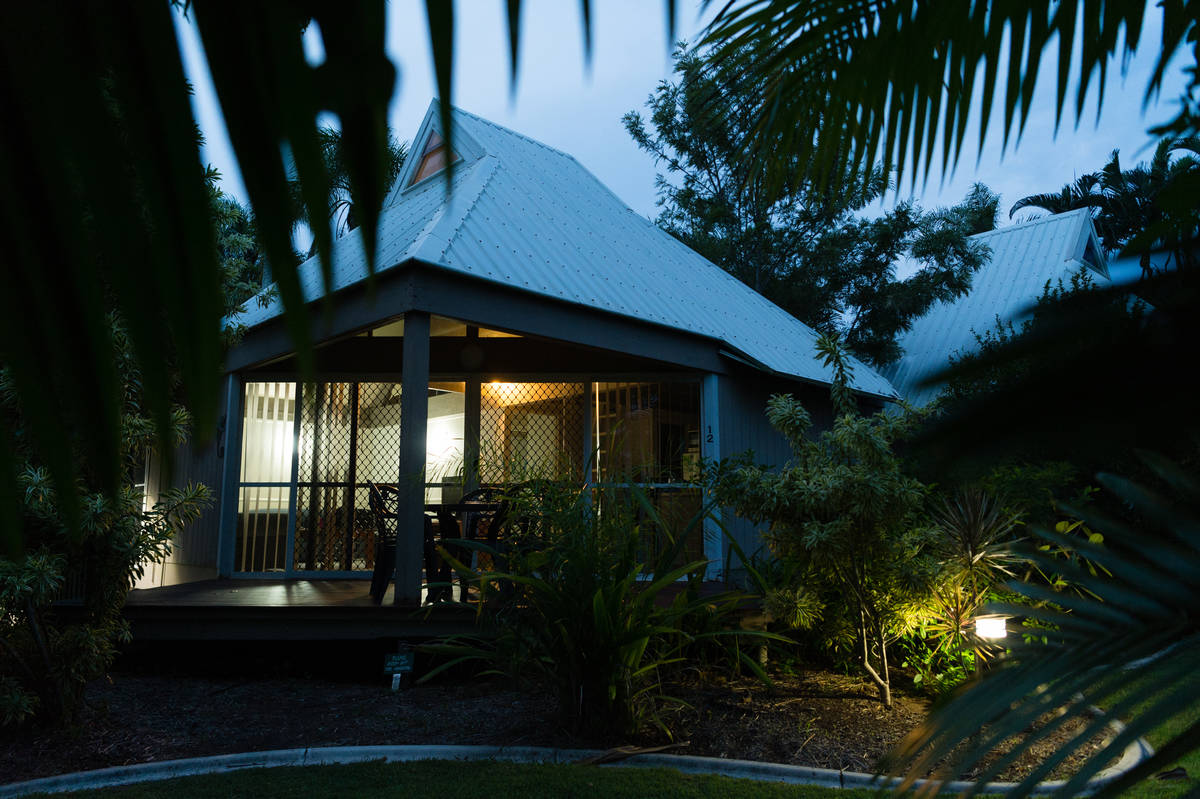 View of Kelly's Beach eco-resort cabin at dusk through palm fronds