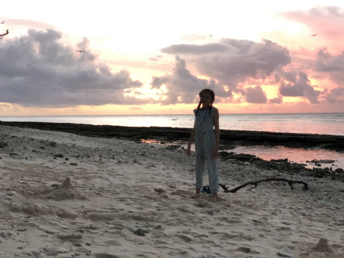 Young girl stands on beach at sunset on Lady Musgrave Island
