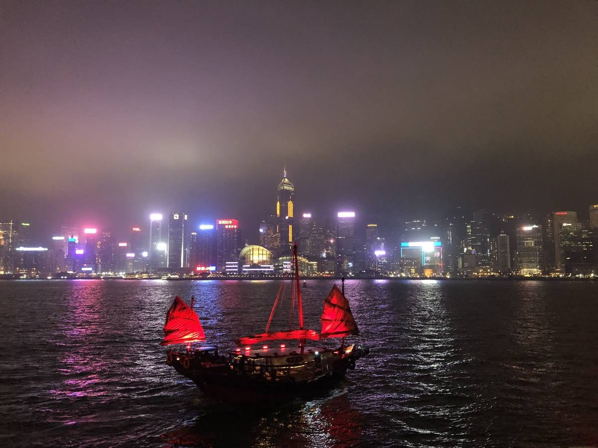 Traditional junk boat and lights on Victoria Harbour at night