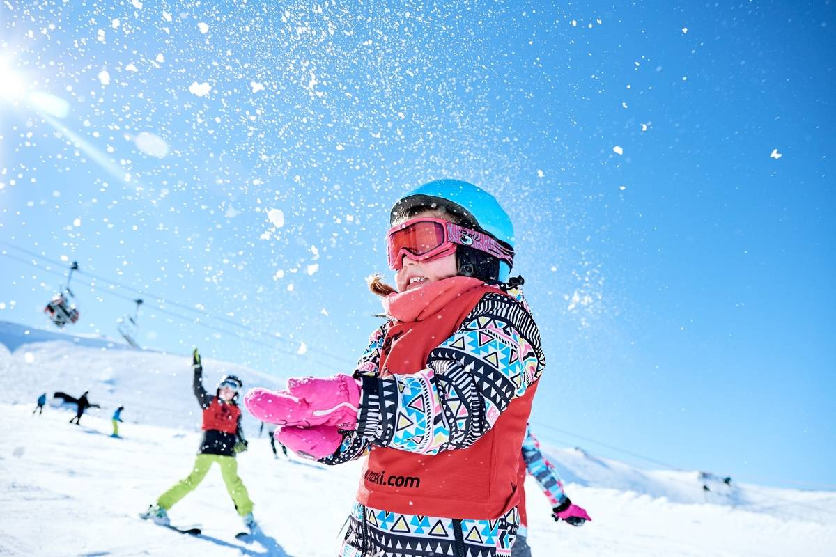 Young girl in ski gear throws snow in the air, blue sky and sun shining Mt Hutt Ben Rogers Tourism NZ