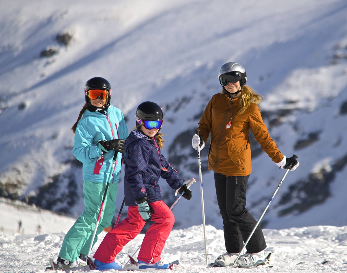 Three girls smiling for a photo in stylish ski gear, mountains in the background.
