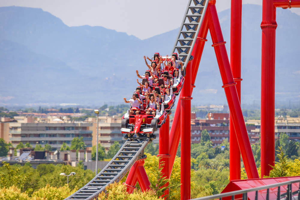 Theme park-goers wave hands and scream as they ride on the Ferrari rollercoaster