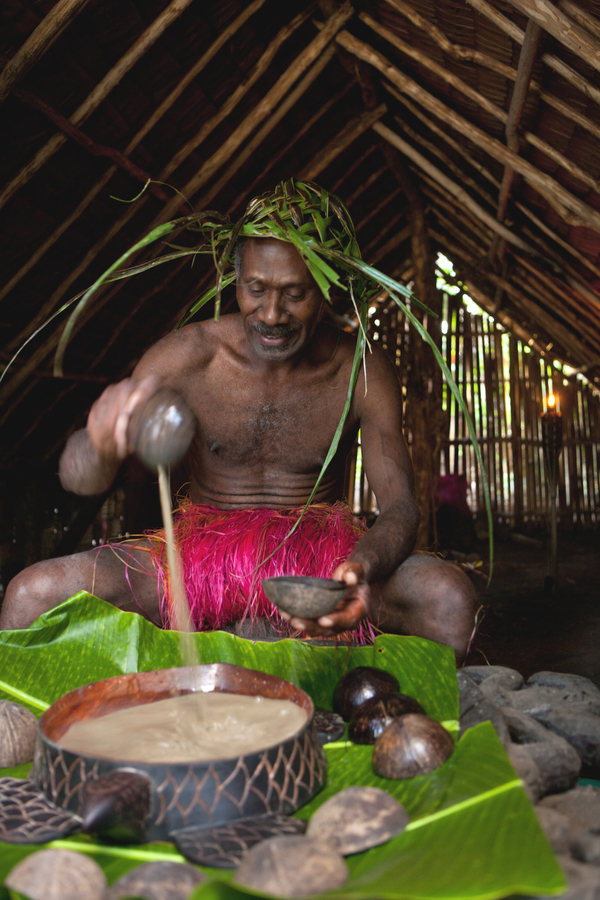 A man sits in a hut pouring kava